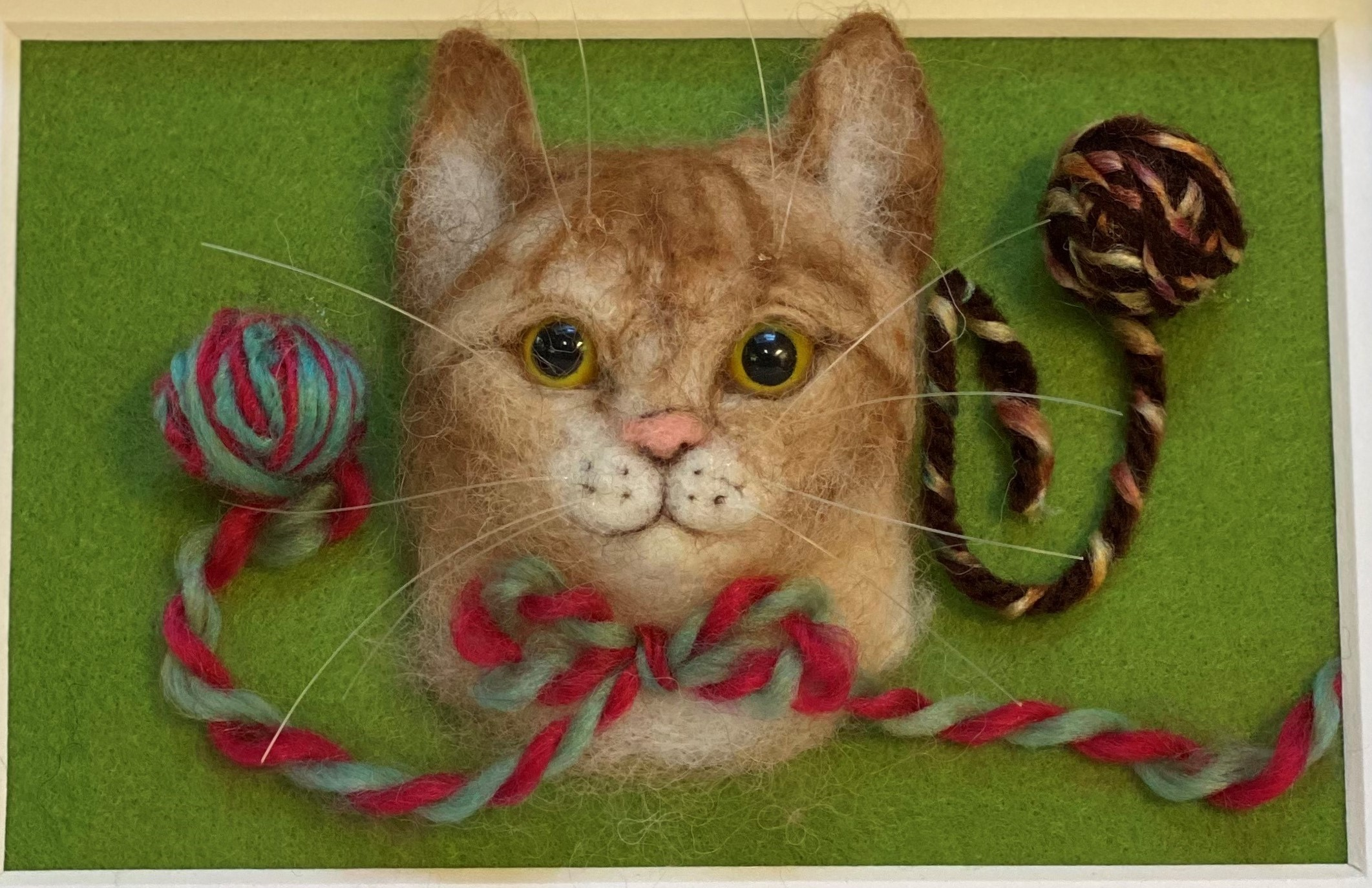 A 3D orange, brown, and white tabby cat head created through needle felting sits on a green background with two balls of yarn.